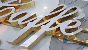 Lettere in ottone lucido a luce diretta con fronti in metacrilato installate su canaline in ottone